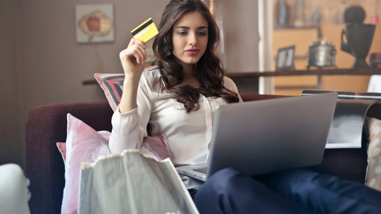 a women holding a credit card and a laptop