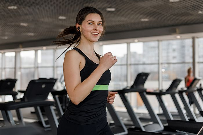 Woman using Redux Buds while working out