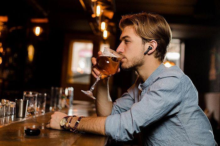 A man using xfyro headphones in a bar