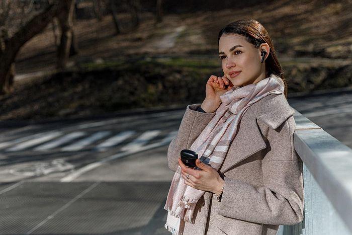 a woman using xfyro headphones outdoors